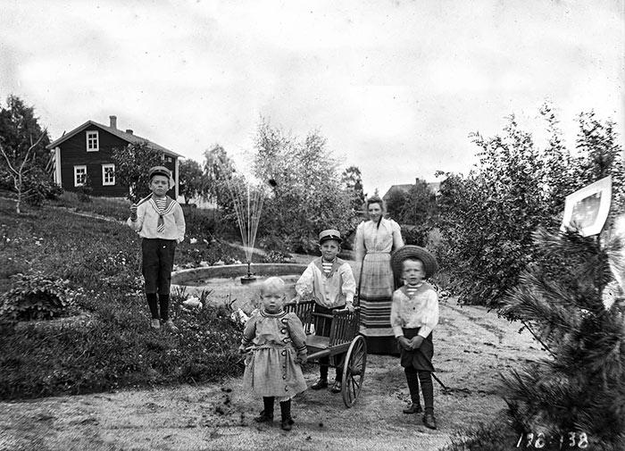 Lapsia pihaleikeissä Saarijärvellä 1800–1900-lukujen vaihteessa. Pihaa koristivat suihkulähde ja istutusten reunustamat hiekkakäytävät. Kuva: Jenny Timgren / Keski-Suomen museo.