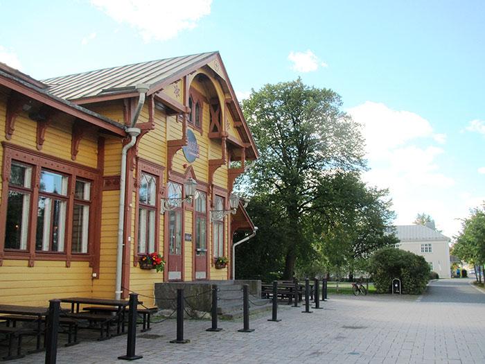 Jyväskylän vanhassa asemarakennuksessa toimii baari. Rakennuksen vieressä on pieni puistoalue, jonka puustorivit muistuttavat vanhasta rautatiemiljööstä. Kuva: Tiia Seppänen / Keski-Suomen museo.