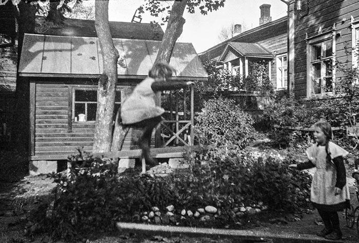 Keinulaudalla hyppiminen oli suosittu pihaleikki. Tässä tytöt hyppivät Jyväskylän Vaasankatu 15:sta pihassa 1920-luvulla. Kuva: Keski-Suomen museo.