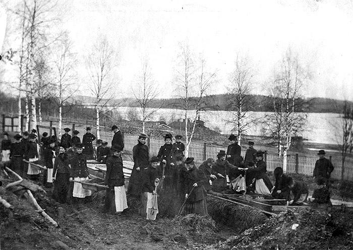 Jyväskylän seminaarin naisoppilaita puutarhanhoidon opetuksessa kevätaikaan seminaarin puutarhassa 1900-luvun alussa. Kuva: G. A. Stoore / Keski-Suomen museo.