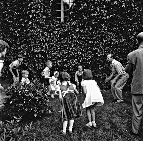 Lasten leikkihetki Jyväskylän vanhan pappilan puutarhassa vuonna 1955. Kuva: Usko Karvalo / Keski-Suomen museo.
